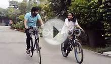 clip 49857436: Tracking shot of a young couple riding bicycle